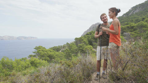 Hiking couple taking phone pictures on nature hike using smartphone on Mallorca Live Action