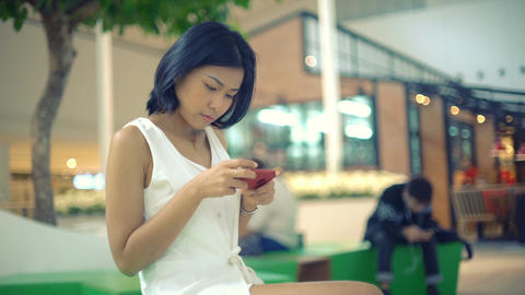 Thai Lady sits in shopping center and typing on smartphone ビデオ