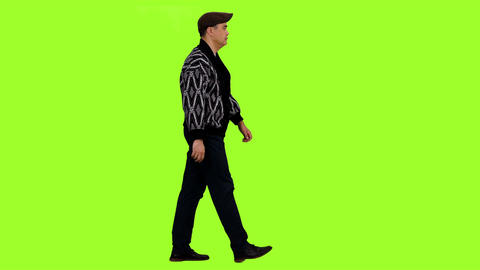 Side view of man in cardigan and flat cap walks on green screen background Footage