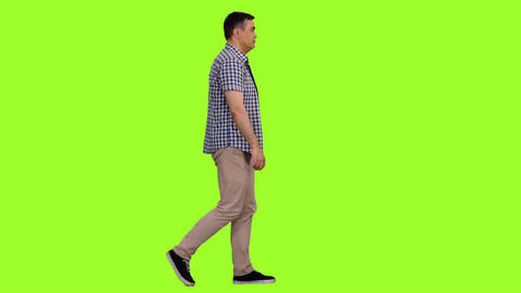 Side view of a male in plaid shirt walks on green screen background, Chroma key Footage