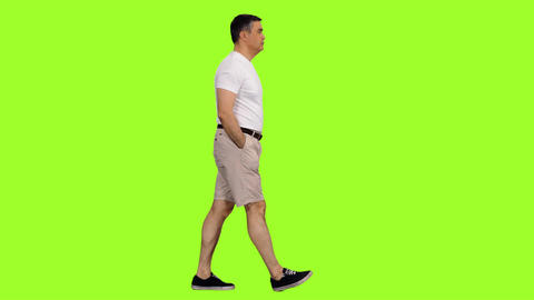 Man in white t-shirt and shorts walks with hands in pockets on green screen Footage
