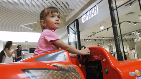 Pretty Little Girl in Pink T-shirt Rides on Cool Red Toy Car Footage