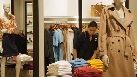 Brunette Woman Walks along Female Store Choosing New Sweater Footage