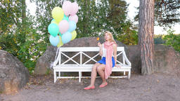 Blonde girl sit on bench and lick lollipop, pack balloons float in air Footage