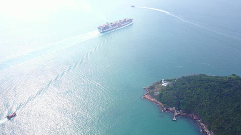 Container carrier ship sail near Green Island, high aerial shot, turquoise water Footage