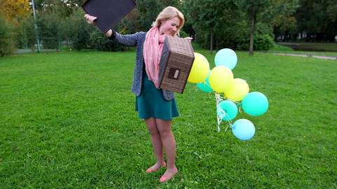 Balloons move and fly up to box, young woman stay at park and show magic Footage