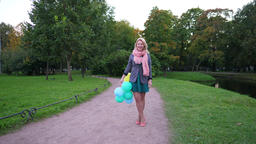 Cheerful young woman stay and look to camera, hold balloons in hand, go away Footage