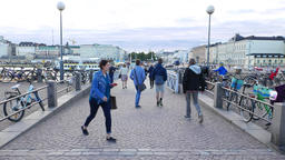 Pedestrian bridge at Helsinki port, people walk by, bicycles parked at handrails GIF