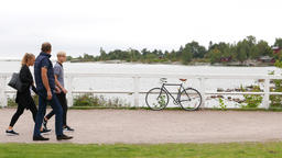 European family of four walk on shore in Kaivopuisto park, bike parked Live Action