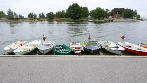 Row boats sway on water along bank, green trees on island across channel Footage