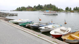Small fiberglass boats moored along embankment road, cutter sail at channel Footage