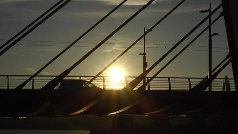 Modern tram ride on bridge, silhouetted view, sun shine through vehicle Footage