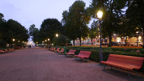 Empty wide walkway of Esplanadi park at evening twilight, wooden benches Live Action