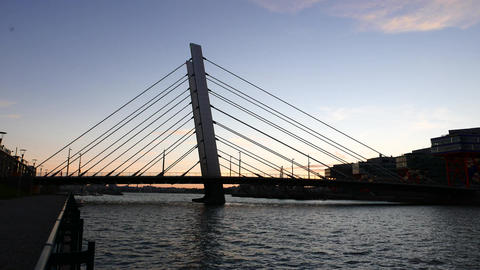 Modern cable-stayed bridge silhouetted against clear sunset sky Live Action