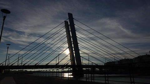 Silhouetted view at modern cable-stayed bridge, time-lapse shot Live Action