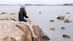 Thoughtful woman sit on large stone at Baltic sea shore, look at distance Live Action