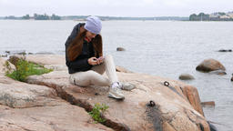 Woman sit on stone at cool shore, texting messages using smartphone Live Action