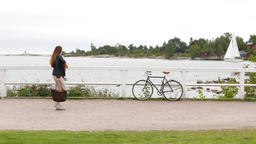 Young woman walk at waterfront of Kaivopuisto park, stop and look to small yacht Live Action