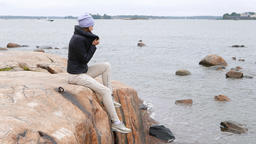Young woman sit on large stone at sea shore, shiver on cool autumn breeze Live Action