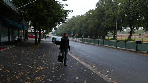 Young woman walk alone at Helsinki street in dusk, autumn season Live Action