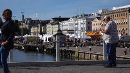 Mature man take picture of Helsinki south port, adult people walk by Live Action