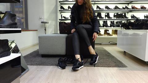 Woman finish choosing new sneakers at shoeshop, take off and put on old, go away Live Action