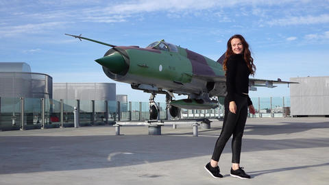 Slender woman pose against jet fighter aircraft set for display, slow motion GIF