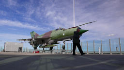 Aged man toddle against jet fighter aircraft set for display at roof Footage