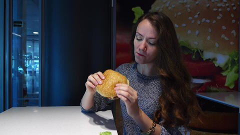 Young woman eat large burger with beef, salad leaf drop down on table Live Action