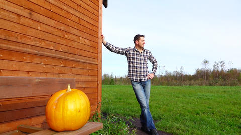 Orange mature pumpkin on wood bench, man pose on background Live Action