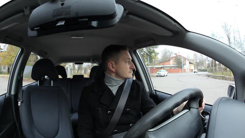 One man sit in car, fasten seat belt and start driving at city suburb GIF