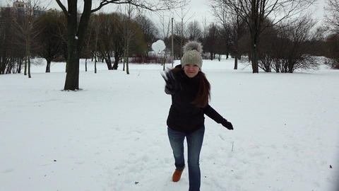 Young woman play snow game, dodge from snowball and throw and hit GIF