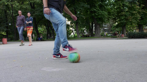 Man with casual clothes plays football tricks outside in city park Image