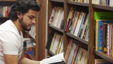 Young man browsing books in a library bookshop Live Action