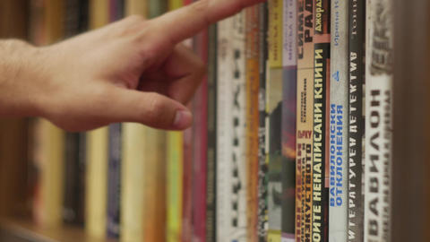 Browsing books in a library by hand - close-up detail Footage