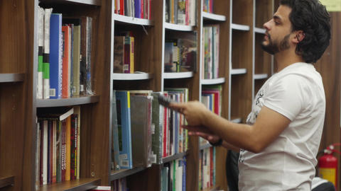 Customer going through books in a bookshop Live Action