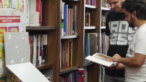 Man shows a book to his friend at a bookstore Footage