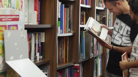 Two friends browsing books in a library store Live Action