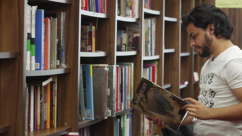 Young man reading encyclopedia in a library bookstore Footage