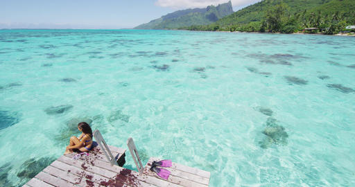 Luxury resort hotel travel woman enjoying holiday sitting after ocean swim Live Action
