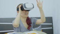 Young cheerful woman wearing virtual reality headset playing 360 VR video game Filmmaterial