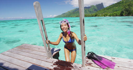 Tahiti travel vacation woman coming up on overwater bungalow from snorkel swim Live Action