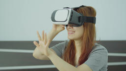 Young cheerful woman wearing virtual reality headset playing 360 VR video game ビデオ