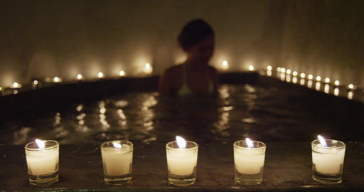 Woman legs relaxing at jacuzzi - focus on candles Footage