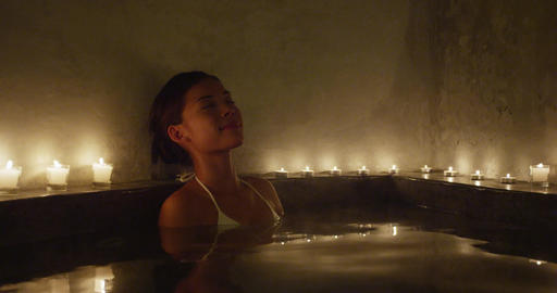 Jacuzzi spa woman relaxing in hot tub whirlpool enjoying bath with candlelight Live Action