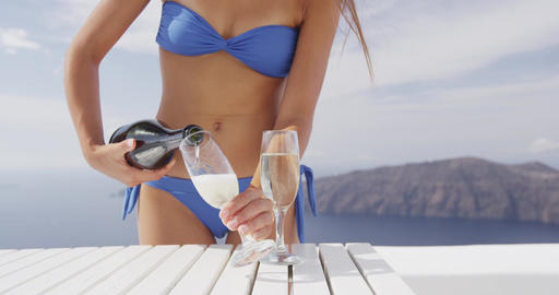 Bikini woman serving two glasses of sparkling wine Footage