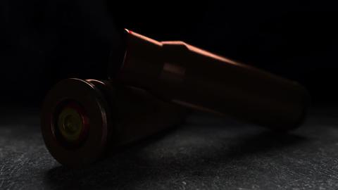 Slow motion macro animation of falling smoking gun cartridge. War, crime, shot ビデオ