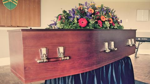 closeup shot of a colorful casket in a hearse or chapel before funeral or burial フォト