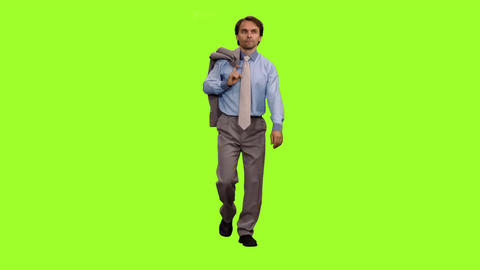 Businessman with suit jacket in hand walks on green screen background Footage