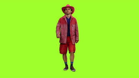 Man in red jacket, shorts and pink cowboy hat walks on green screen background Bild
